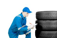 American technician examining tires on studio. American man technician examining a pile of tires and write the report at the clipboard, isolated on white Royalty Free Stock Photo