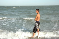 American Teen. The profile of a teenage american boy standing by the ocean. He is looking off to his side. Room for text to the left stock image