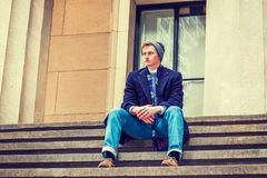 American teenage college student sitting on stairs outside in wi. American teenage college student wearing blue long woolen overcoat, scarf, jeans, leather shoes Stock Images