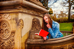 American Teenage Girl Reading Book Outside on Campus in New York Royalty Free Stock Photography