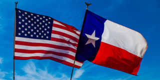 Texas Flag backed by the American flag. American and Texas Flag flying in the breeze stock images
