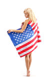 American tiptoe. Young woman with blonde long hair  in American flag stand tiptoe on a white backgrund Stock Photos
