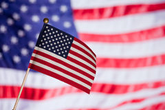 American toy flag over other big flag. Stock Images