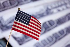 American toy flag over US dollars banknotes. Stock Photos