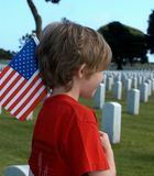 American Tragedy. A grieving child with a flag in a military cemetery Royalty Free Stock Photography