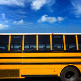 American typical school bus side view. On blue sky day royalty free stock image