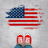 American Urban Youth Concept. Feet in Red Sneakers from Above Standing in front of Grunge USA Flag Royalty Free Stock Image