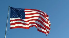American USA flag on a flagpole waving in the wind
