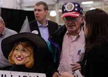 American veteran John Strong with Hillary Clinton House of Horrors Doll speaks with concerned woman. Royalty Free Stock Photos