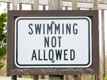 An american warning sign at the beach with man swim and not symbol, Caution No Swimming allowed Royalty Free Stock Images