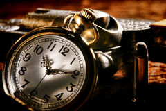 American West Antique Pocket Watch and Outlaw Gun. American West Legend outlaw antique pocket watch keeping time and leaning against a loaded bandit revolver gun Stock Photo