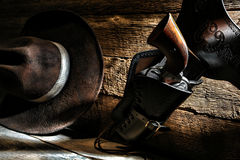 American West Cowboy Gun Holster and Western Hat. American West Legend cowboy vintage revolver gun in antique leather holster hanging on a ranch wood wall with Royalty Free Stock Photos