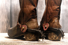 American West Legend Cowboy Boots and Riding Spurs. American West rodeo cowboy traditional leather boots distressed and worn rear heels with antique Western royalty free stock image