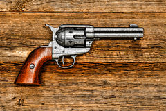American West Legend Peacemaker Revolver on Wood. American West legend Peacemaker old style revolver antique six-shooter weapon gun on aged wood board stock photos