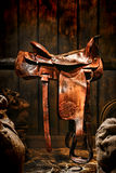 American West Legend Rodeo Cowboy Western Saddle. American West legend authentic rodeo cowboy used and worn brown leather western saddle on a wood rail in an old stock photography