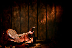 American West Legend Rodeo Cowboy Western Saddle. American West legend traditional rodeo cowboy authentic worn and used brown leather western saddle in an old Stock Images
