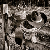 American West Legend Rodeo Western Saddle on Fence. American West Legend rodeo cowboy hat and roping lariat lasso atop an authentic weathered leather western royalty free stock photo