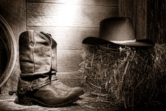 American West Rodeo Cowboy Boots and Hat in Barn. American West rodeo authentic leather roper boots and traditional western black felt hat on a bale of straw hay Stock Photos