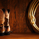 American West Rodeo Cowboy Boots and Lasso Lariat. American West rodeo cowboy traditional leather boots with spurs and authentic Western lasso lariat on barn stock image