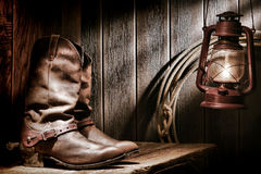 American West Rodeo Cowboy Boots in Old Ranch Barn. American West rodeo cowboy traditional leather roper boots with authentic Western riding spurs on an old wood stock photo