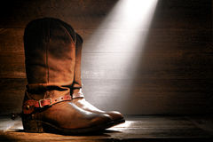 American West Rodeo Cowboy Boots and Riding Spurs. American West rodeo cowboy traditional leather roper boots with Western riding spurs in an old ranch wood barn royalty free stock photo