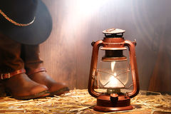 American West Rodeo Cowboy Gear and Kerosene Lamp. American West rodeo cowboy gear with hat atop authentic leather roping boots and lasso lariat with antique Stock Images