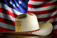American West Rodeo Cowboy Hat and American Flag. American West rodeo cowboy traditional white straw hat over waving old and antique historic US flag at a stock photo