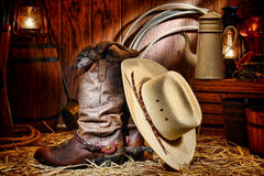 American West Rodeo Cowboy Hat and Boots in a Barn. American West rodeo cowboy traditional white straw hat resting on leather working rancher roper boots with royalty free stock photos