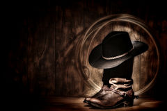 American West Rodeo Cowboy Hat on Boots and Lariat. American West rodeo cowboy traditional black felt hat resting atop worn leather working rancher roper boots royalty free stock photos