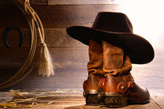American West Rodeo Cowboy Hat on Boots and Lasso. American West rodeo cowboy traditional black felt hat resting on worn leather working rancher roper boots with stock images