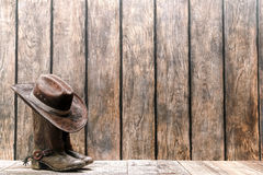 American West Rodeo Cowboy Hat on Boots with Spurs. American West rodeo brown felt cowboy hat atop worn and dirty traditional leather boots on a wood deck in stock images