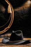 American West Rodeo Cowboy Hat and Lariat Lasso. American West rodeo cowboy black felt hat and lasso hanging on a grunge wall Stock Photography