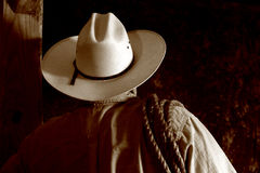 American West Rodeo Cowboy with Hat and Lasso. American west rodeo cowboy with white hat and lasso rope on his shoulder viewed from back in nostalgic sepia Royalty Free Stock Photos