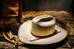 American West Rodeo Cowboy Hat on Lasso with Boots. American West rodeo traditional white straw cowboy hat on an authentic Western lariat lasso with roper stock photography