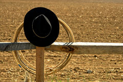 American West Rodeo Cowboy Hat and Lasso on Fence. American West rodeo cowboy hat and lasso on a wood post fence near a ranch dusty earth field Stock Photography