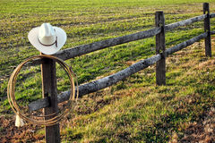 American West Rodeo Cowboy Hat and Lasso on Fence. American West rodeo vintage cowboy hat and authentic lariat lasso hanging on a ranch fence post near a prairie stock photography