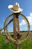 American West Rodeo Cowboy Hat and Lasso on Post. American West rodeo cowboy hat and lasso rope on a wood post fence on a ranch field under blue sky Royalty Free Stock Images