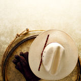 American West Rodeo Cowboy Hat and Lasso Rope. American West rodeo cowboy white hat and authentic Western lariat style lasso with hondo loop on smooth grunge Royalty Free Stock Photo