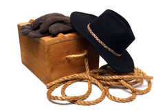 American West Rodeo Cowboy Hat and Old Ranch Tools. American West rodeo cowboy hat and traditional ranch tools with gloves and rope on an antique wood box Royalty Free Stock Photography