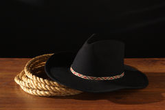 American West Rodeo Cowboy Hat and Ranching Rope. American West rodeo cowboy black felt hat and ranching rope on a wood table Royalty Free Stock Photo