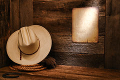 American West Rodeo Cowboy Hat and Rope in Barn. American West rodeo cowboy white straw hat and authentic western rope lasso on weathered wood floor in an old royalty free stock image