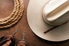 American West Rodeo Cowboy Hat with Spurs and Rope. American West rodeo cowboy traditional white straw hat with roping lasso rope and vintage western riding stock image