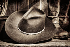 American West Rodeo Cowboy Hat and Western Boots. American West rodeo cowboy felt hat and authentic leather western riding boots with vintage ranching gear on Stock Image