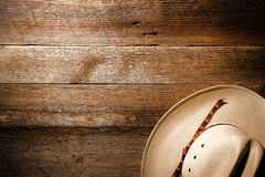 American West Rodeo Cowboy Hat on Wood Background. American West authentic white straw cowboy hat on old and aged western saloon floor wood plank background stock images