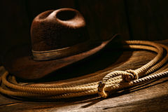 American West Rodeo Cowboy Lariat Lasso and Hat. American West authentic rodeo cowboy lariat lasso honda noose with end loop rawhide speed burner on weathered Stock Image