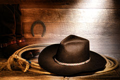 American West Rodeo Cowboy Hat and Lasso in Barn. American West rodeo cowboy black felt hat on an authentic Western roping lariat lasso with leather riding boots royalty free stock photos