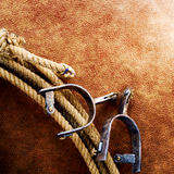American West Rodeo Cowboy Lasso and Roping Spurs. American West rodeo cowboy lariat lasso with cutting and roping spurs on old brown leather grunge background royalty free stock photo