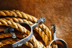 American West Rodeo Cowboy Lasso and Roping Spurs. American West rodeo cowboy ranching rope with western riding spurs on old brown leather grunge background royalty free stock photography