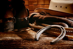 American West Rodeo Cowboy Old Horseshoe and Gear. American West rodeo old horseshoe on lariat lasso and roping work gloves with Western horse rider gear with royalty free stock images