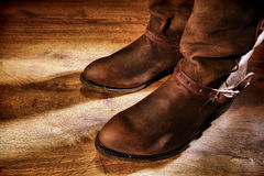 American West Rodeo Cowboy Ranching Boots on Wood. American West rodeo cowboy traditional working ranching boots with old leather Western riding spur straps on Royalty Free Stock Image